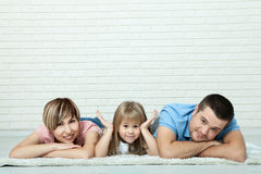 Portrait of baby and her parents lying on carpet in living room. White brick wall background, space for text Stock Photography