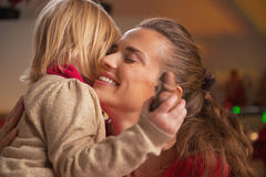 Portrait of baby hugging mother in christmas decorated kitchen Stock Image