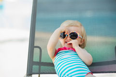 Portrait of baby laying on sunbed. Portrait of baby in swimsuit and sunglasses laying on sunbed Royalty Free Stock Photos