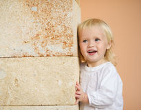 Portrait of baby leaning against wall Stock Photo
