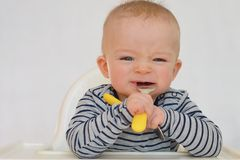Portrait of baby learning to eat with fork and spoon Royalty Free Stock Images