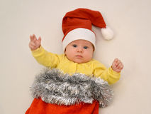 Portrait of the baby in a New Year's suit Santa Claus on a light background a light. Portrait of the baby in a New Year's suit Santa Claus royalty free stock images