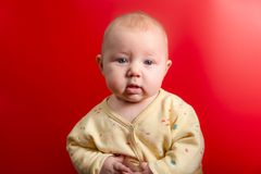 Portrait of a baby on a red background, newborn girl close-up in the studio royalty free stock photos