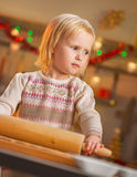 Portrait of baby rolling pin dough in christmas kitchen Royalty Free Stock Photos