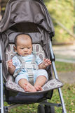 Portrait of baby sit on stroller carriage Stock Photos