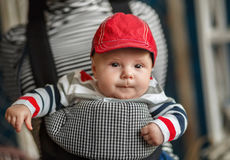 Portrait of a baby sitting in an ergonomic baby carrier. Portrait of a cute baby sitting in an ergonomic baby carrier Stock Images