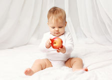 Portrait of baby sitting with red apple on the bed Stock Photos