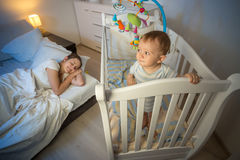 Portrait of baby standing in crib and looking at tired mother th. Portrait of cute baby standing in crib and looking at tired mother that fell asleep Royalty Free Stock Photography