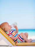 Portrait of baby on sun bed drinking water. Portrait of baby girl on sun bed drinking water Stock Photo