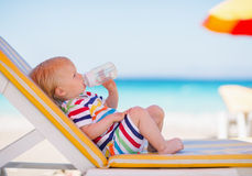 Portrait of baby on sunbed drinking water. Portrait of baby girl on sunbed drinking water Royalty Free Stock Photo