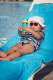Portrait of baby on sunbed drinking water Royalty Free Stock Photography