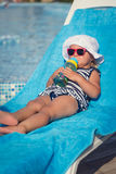 Portrait of baby on sunbed drinking water Stock Photos