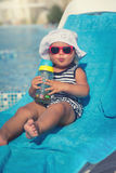 Portrait of baby on sunbed drinking water Royalty Free Stock Photos