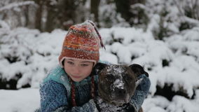Portrait of a baby with a terrier in the winter in the park. A boy plays with a dog in winter. stock footage