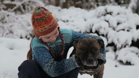 Portrait of a baby with a terrier in the winter in the park. A boy plays with a dog in winter. stock video