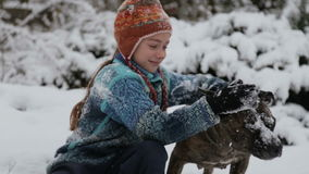 Portrait of a baby with a terrier in the winter in the park. A boy plays with a dog in winter. stock video footage