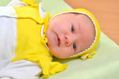 Portrait of the baby in a yellow cap. The child looks directly Royalty Free Stock Images