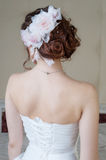 Portrait of back of bride in white dress with hair style and flo Royalty Free Stock Image