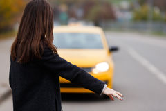 Portrait from the back of brunette woman stopping yellow taxi Stock Photography