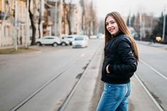 Portrait from back of elegant girl with long hair walking on city background. She has black leather jacket and jeans. She is royalty free stock photography