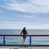 Outdoor portrait from back slim girl in a dress and denim jacket looking at sea