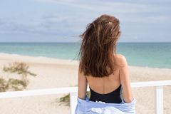 Portrait from the back of young sexy girl standing on a background of beach, sand and sea. She wearing black swimwear, blue shir. Portrait from the back of a Royalty Free Stock Images