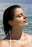 Portrait of a baeutiful woman tanning her face at the beach Stock Image