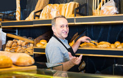 Portrait of  baker with fresh bread smiling in bakery. Portrait of senior american baker with fresh bread smiling in bakery Royalty Free Stock Photo