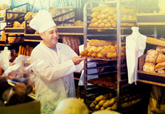 Portrait of  baker with fresh bread smiling in bakery. Portrait of senior russian baker with fresh bread smiling in bakery Royalty Free Stock Photo