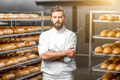 Portrait of a baker. Portrait of handsome baker at the bakery with breads and oven on the background stock photos