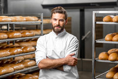 Portrait of a baker. Portrait of handsome baker at the bakery with breads and oven on the background stock photography