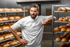 Portrait of a baker. Portrait of handsome baker at the bakery with breads and oven on the background Royalty Free Stock Image