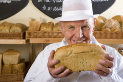 Portrait of baker in white uniform holding loaf of bread Stock Image