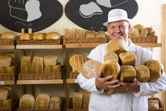 Portrait of baker in white uniform holding loaves of bread Stock Photography