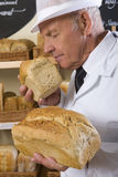 Portrait of baker in white uniform smelling loaf of bread Royalty Free Stock Photo