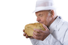Portrait of baker in white uniform smelling loaf of bread, cut out Stock Photo