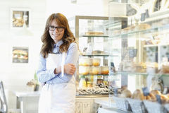 Portrait of bakery shop owner. Smiling, beautiful mature woman. Small business bakery shop owner standing in her store Royalty Free Stock Photos