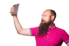 Portrait of bald bearded man with tablet and pink t-shirt. Isolated on white background Royalty Free Stock Photo