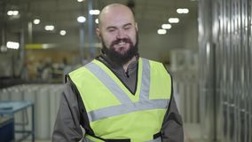 Portrait of bald Caucasian man with beard standing at warehouse, looking at camera and smiling. Happy worker at his