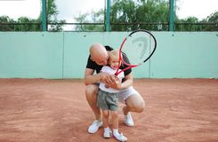 Portrait of the bald father and little daughter on the tennis court. Royalty Free Stock Photo