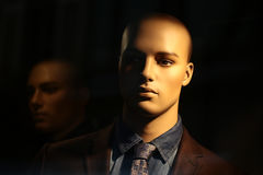 Portrait of bald-headed mannequin. Closeup portrait of illuminated bald-headed fashion mannequin wearing casual male suit made of thready cloth jacket tie shirt Stock Photography