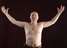 Portrait of a bald man. Close-up portrait on a belt adult bald man with a naked torso and a cross on his chest on a dark background studio Stock Photos