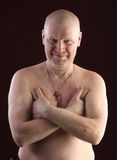 Portrait of a bald man. Close-up portrait on a belt adult bald man with a naked torso and a cross on his chest on a dark background studio Stock Photo