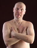 Portrait of a bald man. Close-up portrait on a belt adult bald man with a naked torso and a cross on his chest on a dark background studio Stock Image