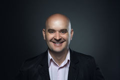 Portrait of a bald smiling, affable man in a suit against a dark background Royalty Free Stock Photo