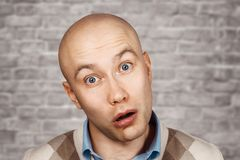 Portrait of a bald stupid surprised guy with open mouth on an brick wall background.  royalty free stock photos