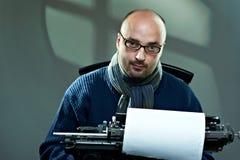 Portrait of a bald writer. Sitting at a typewriter stock image