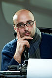 Portrait of a bald writer. Sitting at a typewriter royalty free stock photo