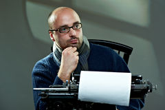 Portrait of a bald writer. Sitting at a typewriter royalty free stock photos