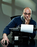 Portrait of a bald writer. Sitting at a typewriter stock images